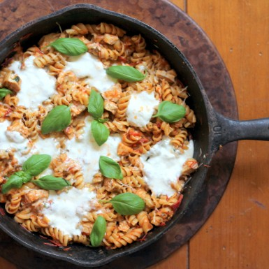 Rotini noodles in a light tomato saurce topped with mozzarella cheese and basil leaves in a skillet