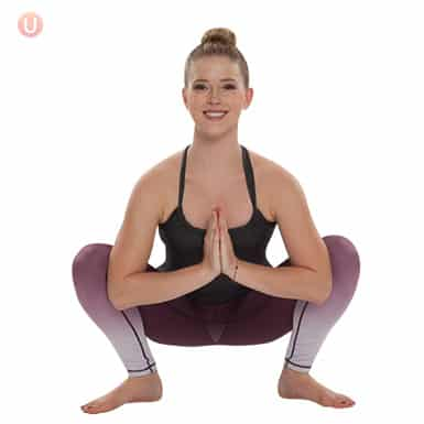 Chloe Freytag demonstrating Yogi Squat Pose in a black tank top and yoga pants